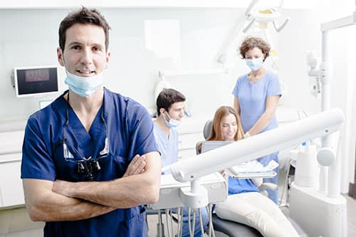 Dental patients and dentists in the office preparing tools wearing custom uniforms.