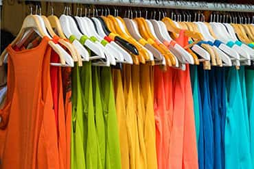 Colourful sleeveless t-shirts hanging, ready to be customized with design or logo.